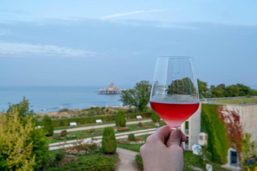 Den Ausblick auf die Ostsee von der Außenterrasse der Strandlounge im Schwesternhotel Strandhotel Ostseeblick mit einem Glas Wein genießen